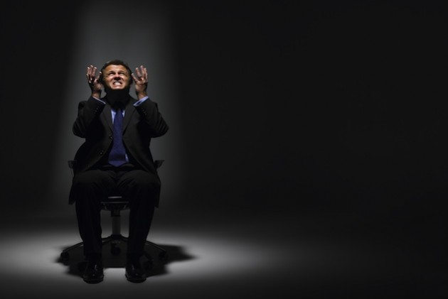 Businessman Sitting In Spotlight